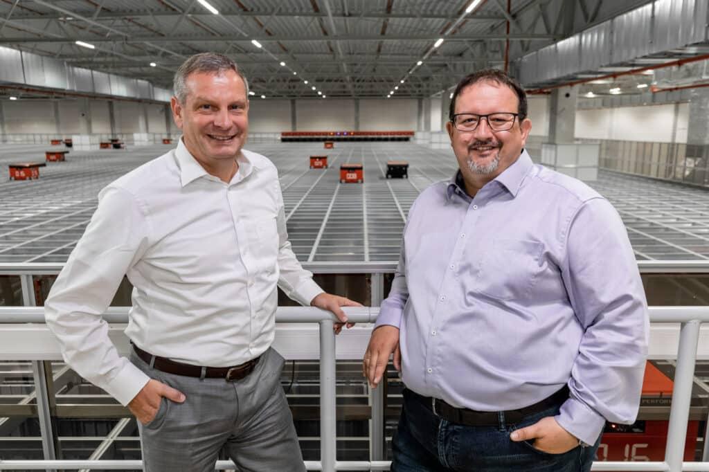 Michael Kawalier und Thomas Rolle stehen vor AutoStore System von TTI
